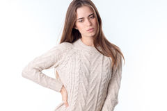 Young girl in white sweater keeps her hand on the side and looks down Stock Photos