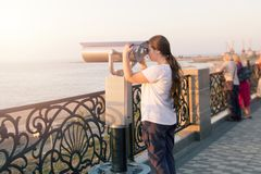 Young girl in white t-shirt looking through a coin operated binoculars on the sea shore. Woman look in touristic telescope on emba royalty free stock image