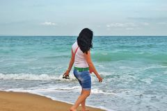 A young girl in a white Tshirt is walking along the sand in the sea. brunette on the shore of the azure sea in Bulgaria royalty free stock photography
