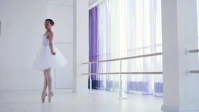 Ballerina in white tutu performances classic ballet dance elements. Young girl in white tutu and pointes performances classic ballet dance elements in ballet stock video