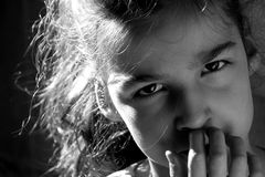 Young girl. Who looks at us with his hands touching the mouth Stock Photography