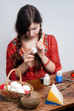 Young girl who is painting an egg for easter Royalty Free Stock Image