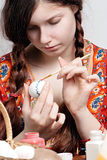 Young girl who is painting an egg for easter Royalty Free Stock Photography