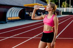 A young girl who participates in sport at the stadium drinking water. Sport background. Outdoor stadium Stock Photos