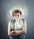 Young girl who smoke. Angry woman briging smoke out of her nose Stock Photography