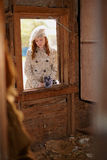 Young girl in  the window. A young girl through the window of a wood building Stock Photos