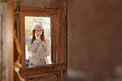 Young girl through a window. A view of a pretty young girl with red hair through a wooden window Royalty Free Stock Images