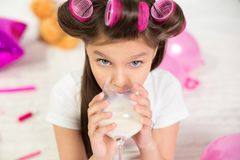 Young girl with wine glass of milk. Charming sweet preschooler having some milk. Portrait of adorable little girl with hair rollers drinking milk from wineglass stock photography