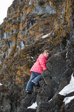 Young Girl climbs the rocks Stock Images