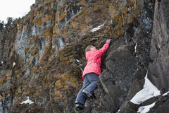 Young Girl climbs the rocks Royalty Free Stock Image