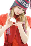 Young girl in winter cap pouring out tablets Royalty Free Stock Photo