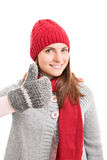 Young girl in winter clothes holding thumbs up Stock Image