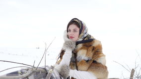 Young girl in winter clothes waiting near fence and looking aside 4K.  stock footage