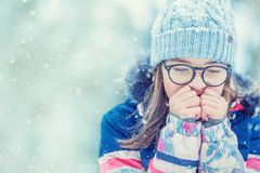 Young girl in winter clothes warming her cold hands.  Stock Image