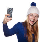 Young girl in winter hat laughing and making selfie. Stock Images