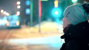 A young girl in a winter hat is standing at the traffic light. Against the background of the night lights of passing. Cars in the city. Steam from mouth and stock video footage