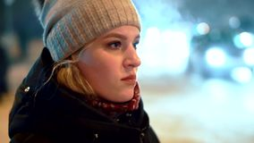 A young girl in a winter hat is standing at the traffic light. Against the background of the night lights of passing. Cars in the city. Steam from mouth and stock footage