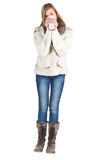 Young girl with winter jacket, blue jeans and boots holding cup Stock Image