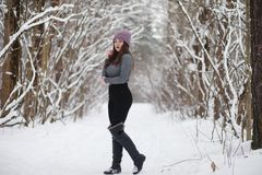 A young girl in a winter park on a walk. Christmas holidays in t royalty free stock photography