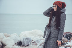 Young girl in winter sea, stones on a background of icy stares into the distance. Girl in a red coat and knitted cap Stock Image