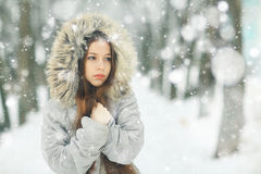 Young girl in winter snowy garden Royalty Free Stock Image