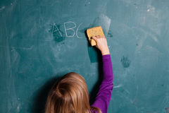Young girl wiping chalkboard with wet sponge Royalty Free Stock Photo