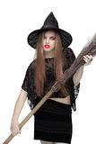 Young girl in witch costume with a broom royalty free stock images