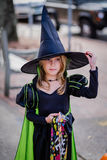 Young girl in witch costume. Attractive young blond girl at Halloween wearing striking witch's outfit comprising long black dress, green lined cloak and tall Royalty Free Stock Photo