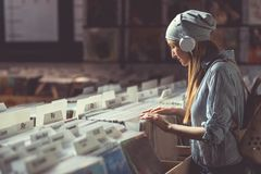 Young Girl With Headphones Browsing Records Royalty Free Stock Images