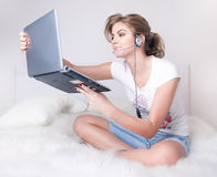 Young girl witn silver laptop and skype headset Royalty Free Stock Image
