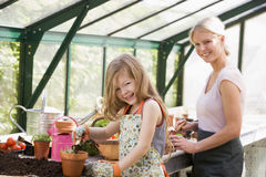 Young girl and woman in greenhouse Stock Photo
