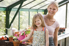 Young girl and woman in greenhouse smiling Royalty Free Stock Image