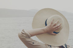 Young girl woman holding her straw hat watching on the ocean. Tr. Avel Vacation Summer Concept. Toning Stock Photo