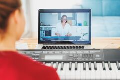 Young girl woman learns to play the piano with a teacher on a video conference from a laptop. The teacher on the screen explains