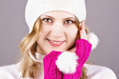 Young girl in a wool hat and gloves. Beautiful young girl in a wool hat and gloves on the grey background Royalty Free Stock Images