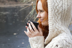 Young girl in  wool sweater drinking a cup of hot drink. Young girl in knitting wool sweater drinking a cup of hot drink Royalty Free Stock Image