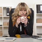 Young girl at work enjoying hot coffee Royalty Free Stock Photography