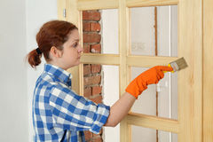 Young girl worker, painting new wooden door Stock Photography