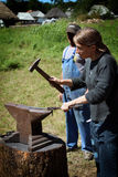 Young girl working as a blacksmith Stock Photography