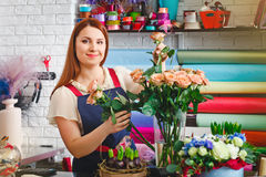 Young girl working in a flower shop, Florist woman makes a bouquet Stock Photos