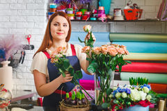 Young girl working in a flower shop, Florist woman makes a bouquet Stock Images