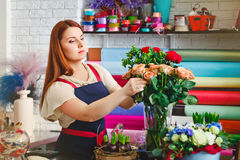 Young girl working in a flower shop, Florist woman makes a bouquet Stock Photo