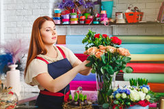 Young girl working in a flower shop, Florist woman makes a bouquet royalty free stock photography