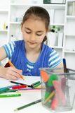 Young girl working on her school project at home. Royalty Free Stock Images
