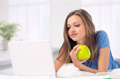 Young girl working with laptop at home holding an apple Royalty Free Stock Image