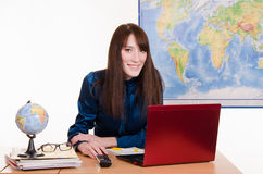 Young girl working on a laptop in the office of travel agency. Young beautiful employee in the office of the travel agency Stock Image
