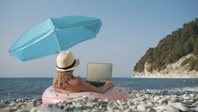 Young girl working on laptop outdoors in summer vacation