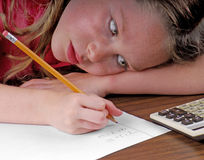 Young girl working on math. Young girl with head on desk working on math problems Stock Photography