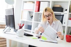 A young girl working in the office with a computer and documents. royalty free stock images