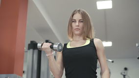 Young girl working out with dumb-bells for biceps in the gym 4K. Young girl working out with for biceps in the gym 4K stock footage